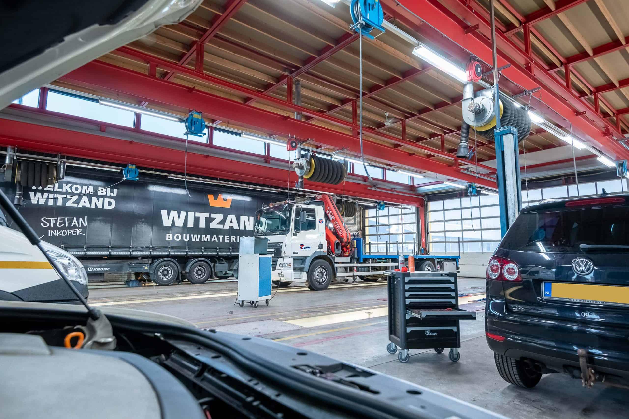 werkplaats met auto's vrachtwagens en werkbussen